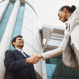 Low angle view of two business executives shaking hands